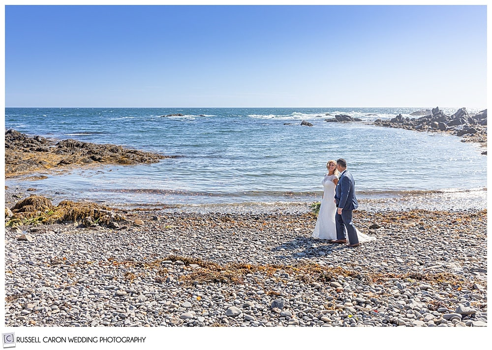 bride and groom walking on a rocky beach in Kennebunkport, Maine