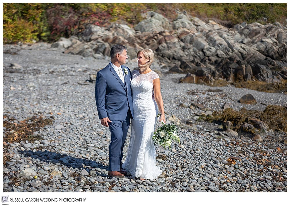 bride and groom standing side by side on a rocky beach in Kennebunkport, Maine