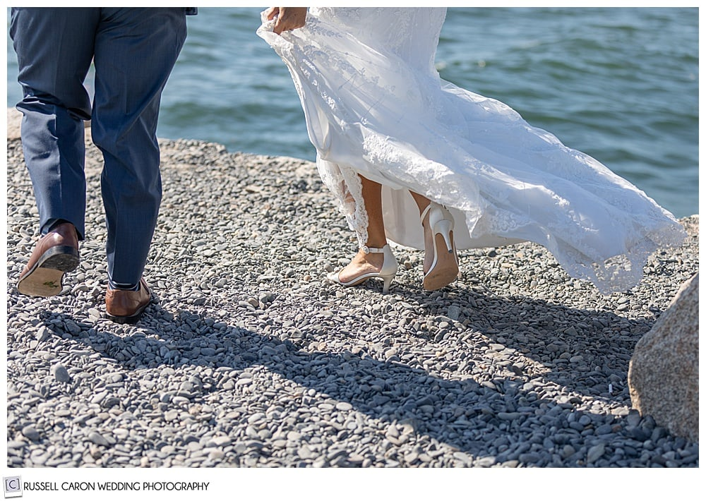 feet of a bride and groom walking on the Kennebunkport, Maine, breakewater