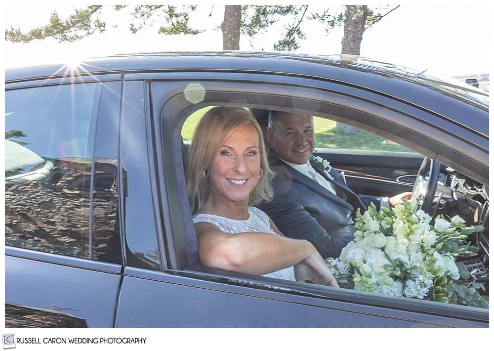 bride and groom sitting in a black car, smiling