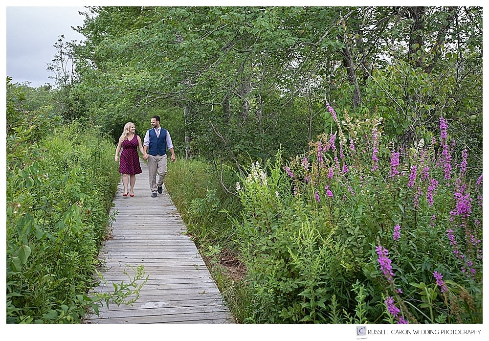 man and woman holding hands, walking on a boardwalk in the woods at Inn by the Sea, Cape Elizabeth, Maine