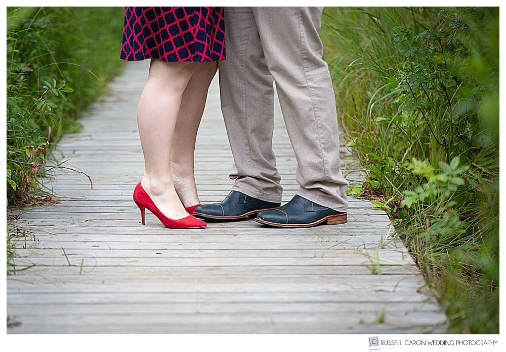photo of man and woman's feet standing together on a boardwalk