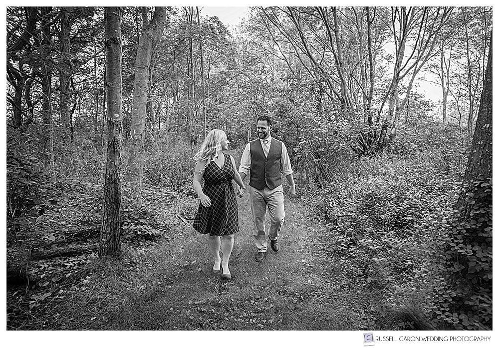 black and white photo of man and woman walking in the woods
