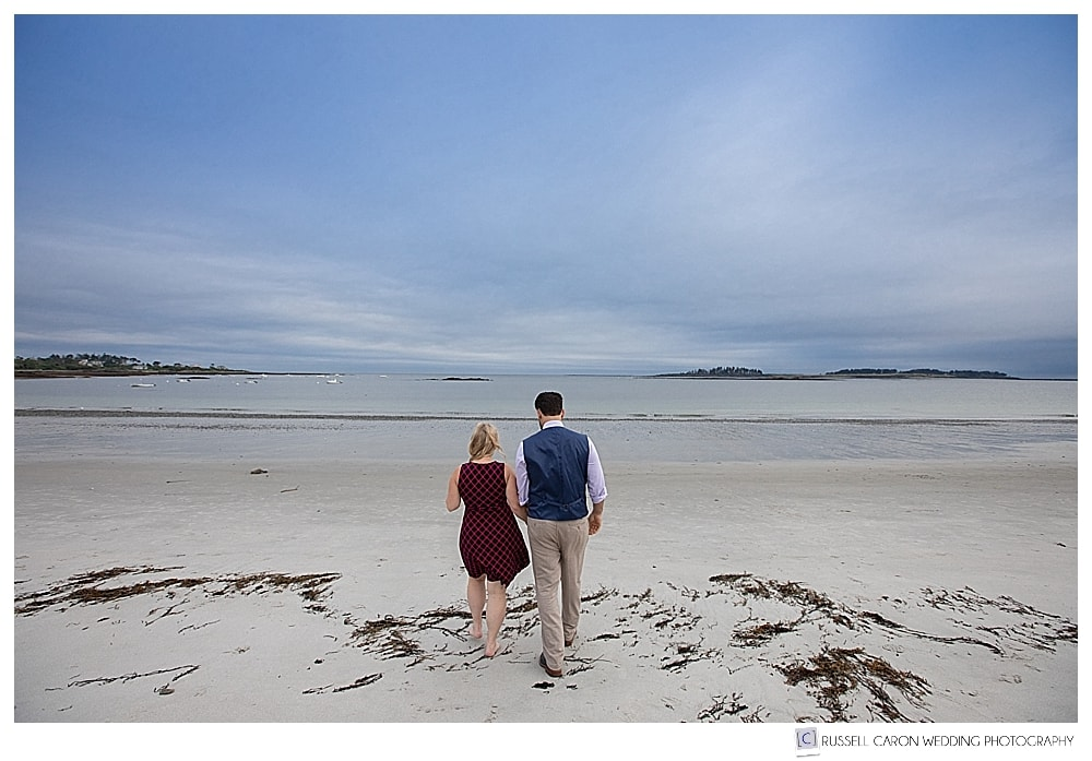 Man and woman walking away, holding hands, on Crescent Beach, Cape Elizabeth, Maine