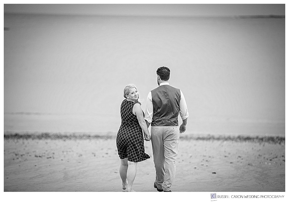 black and white photo of man and woman walking away on the beach, woman is looking over her shoulder at the camera