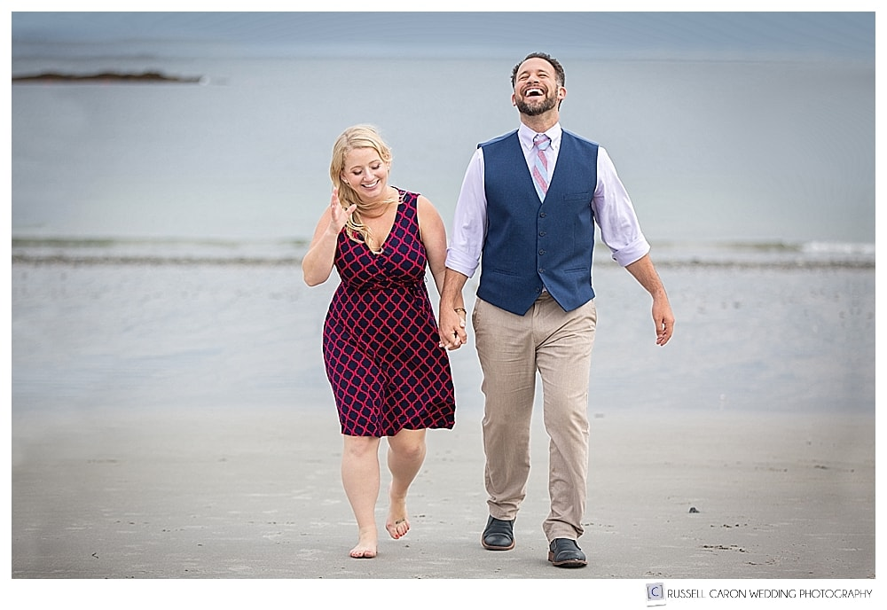man and woman walking together on Crescent Beach, Cape Elizabeth, Maine, holding hands and laughing