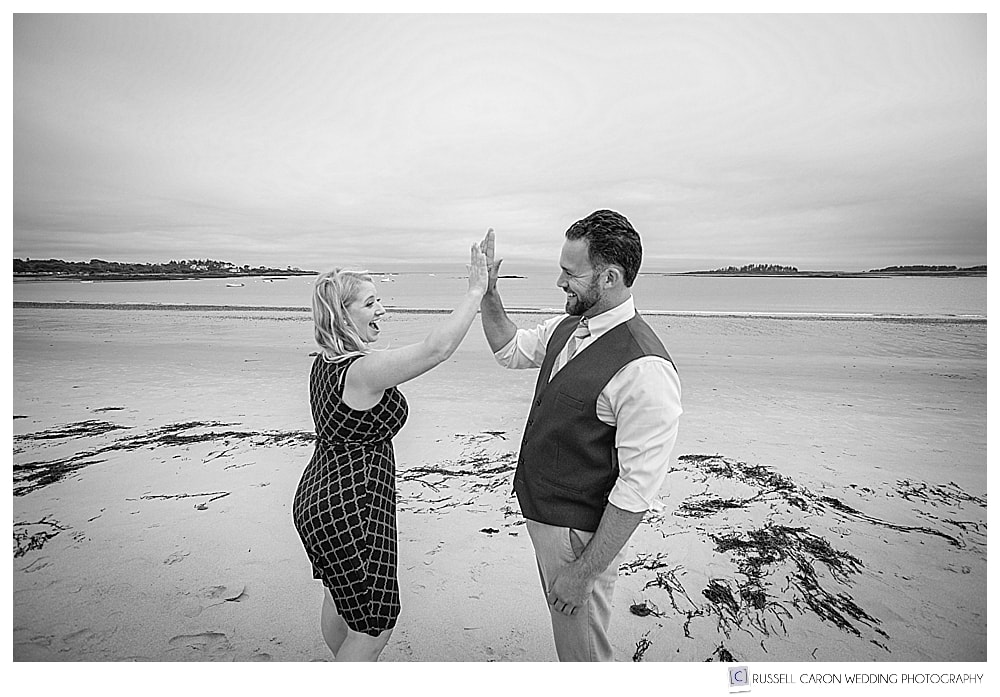 black and white photo of man and woman high fiving on the beach