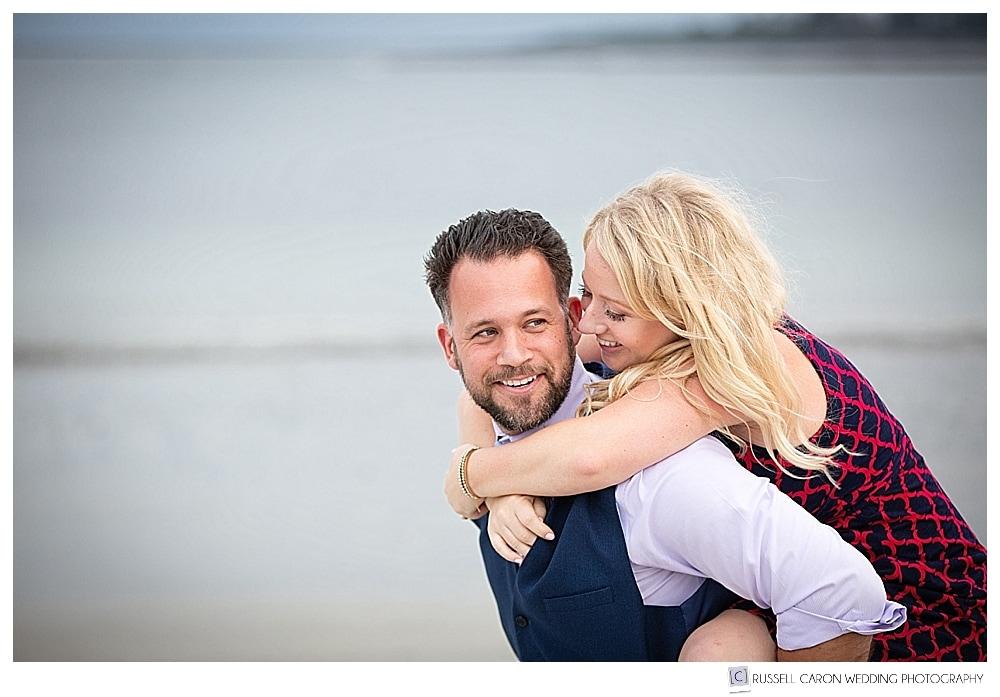 man giving woman piggy back ride on the beach