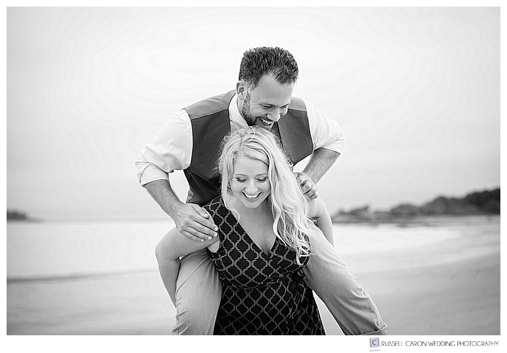 black and white photo of woman trying to give man a piggy back ride at the beach