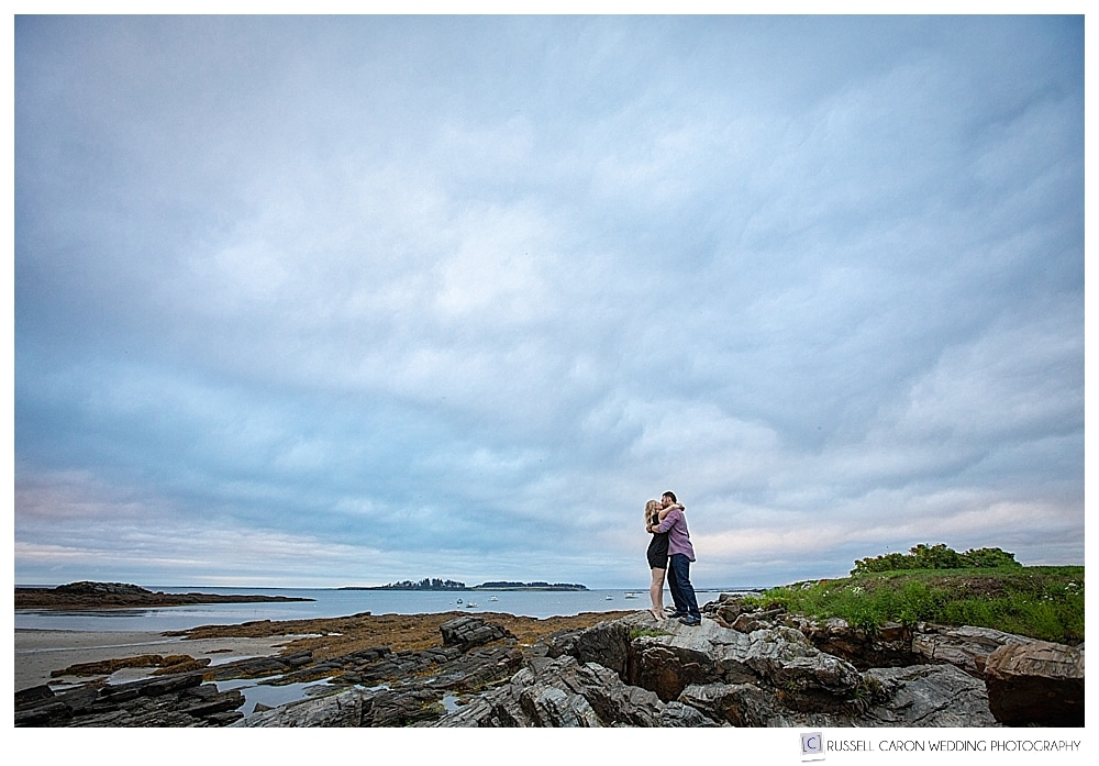 woman and man standing together on the rocks at Kettle Cove, Cape Elizabeth, Maine engagement session