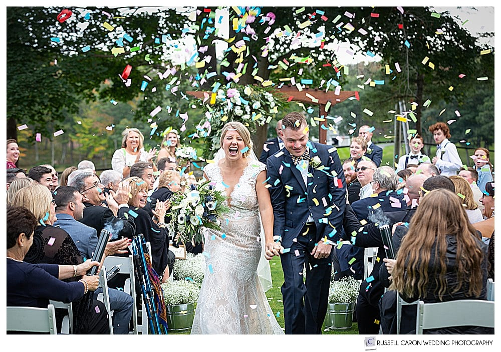 Bride and groom during ecstatic wedding recessional with confetti cannons shooting confetti