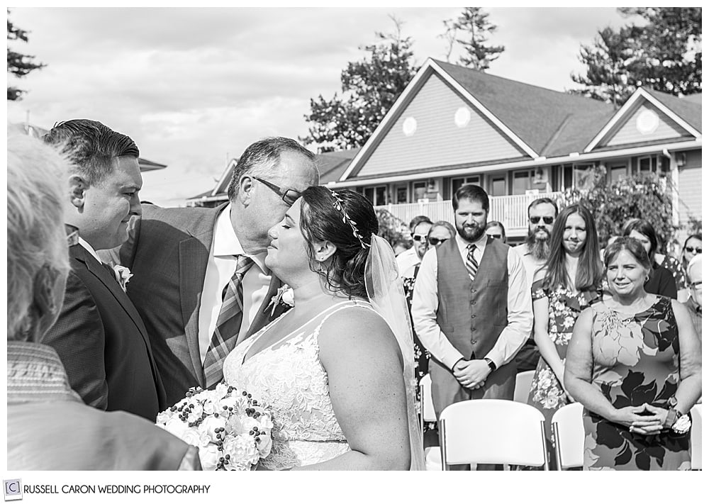 black and white photo of father kissing the bride at the altar