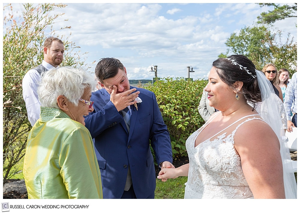 groom wiping his eyes as the bride reaches the altar