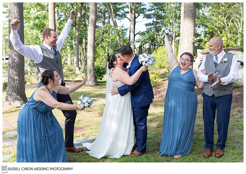 bride and groom kissing while wedding party cheers