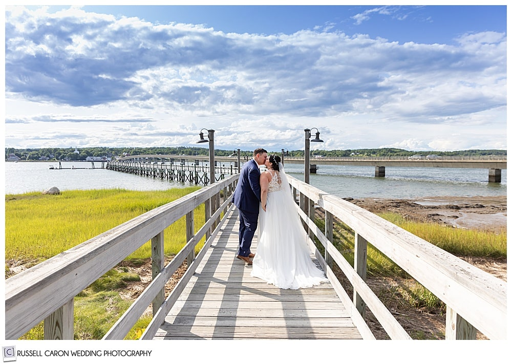 bride and groom kissing on the dock at the Sheepscot Harbour Village Resort, Edgecomb Maine wedding
