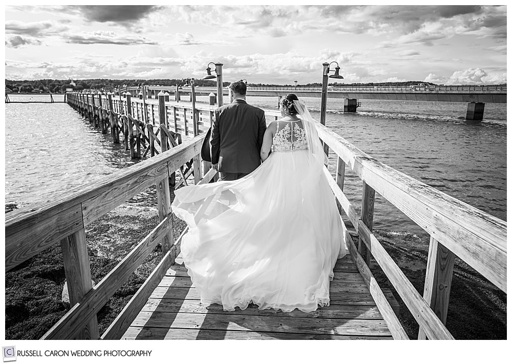 black and white photo of a bride and groom walking on a long dock