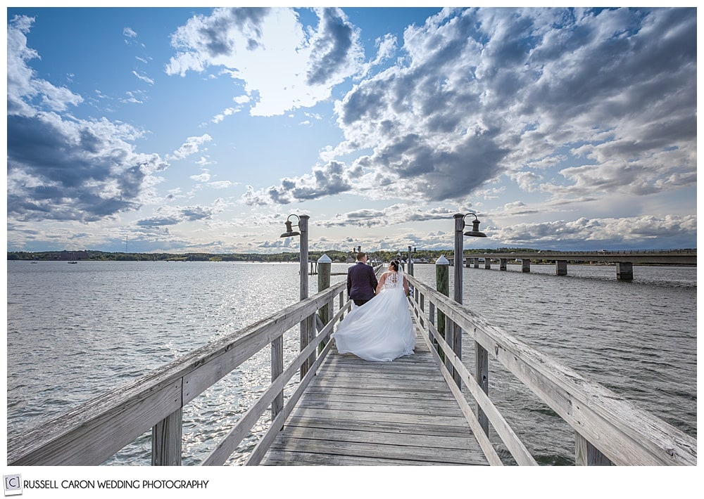bride and groom walking on a dock after their Edgecomb Maine wedding ceremony