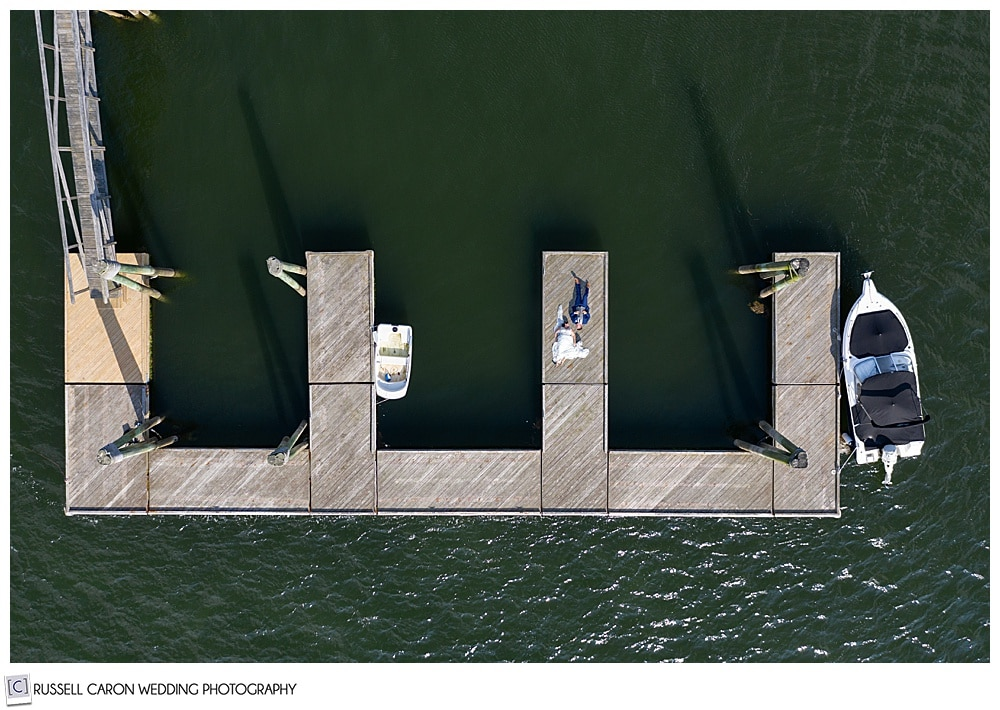 drone photo of a bride and groom on a dock