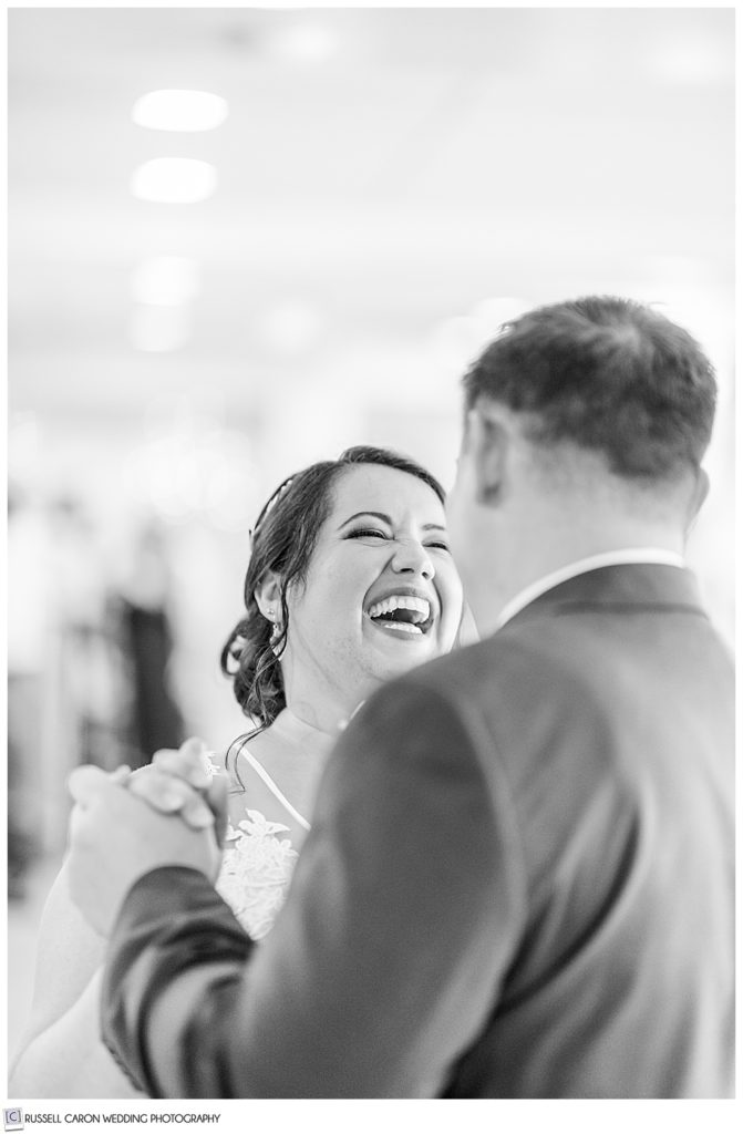 black and white photos of bride laughing with groom during first dance