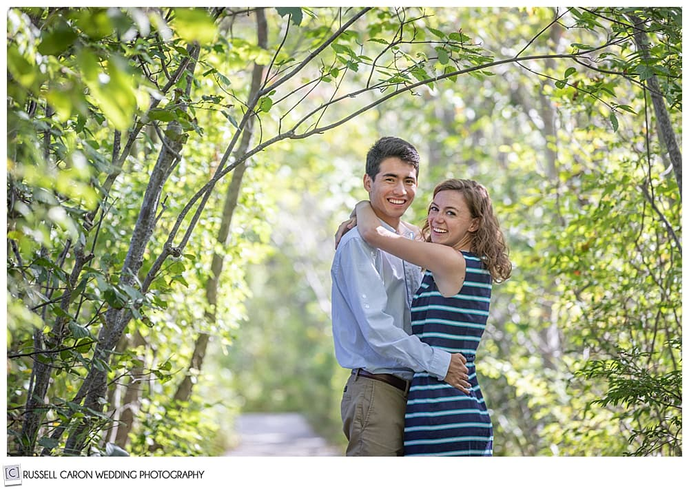 man and woman, in the woods, with their arms around each other, they're looking at the camera