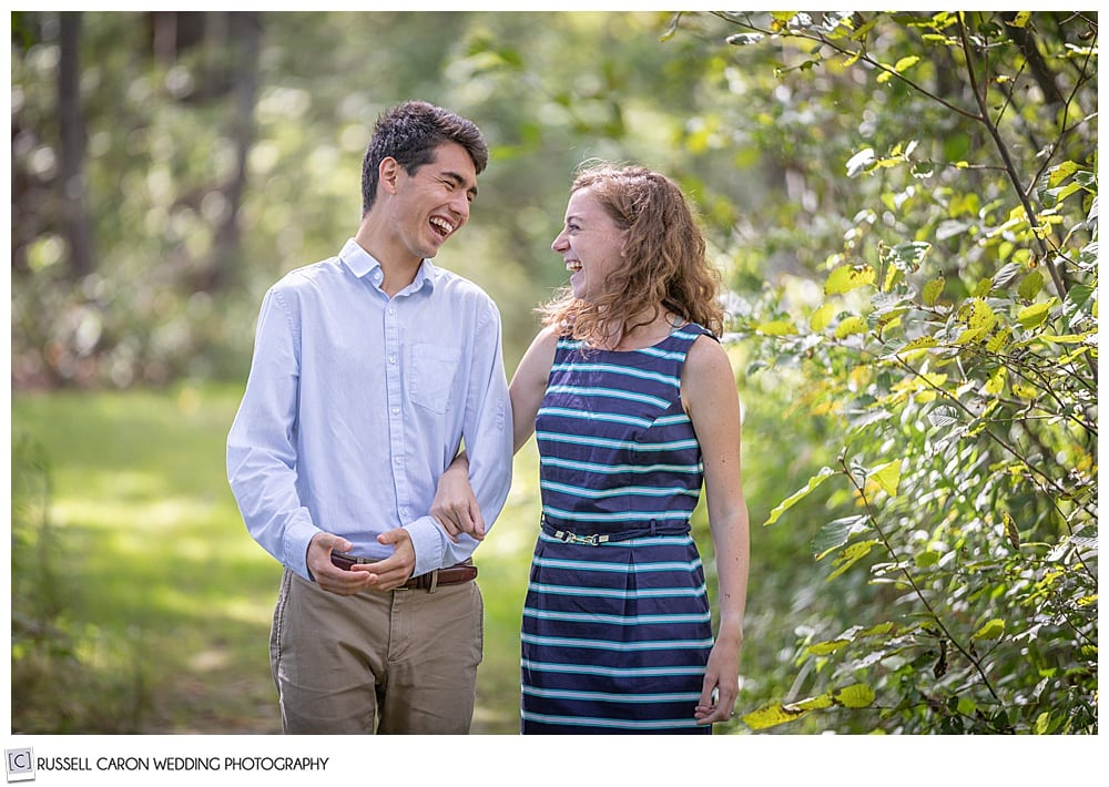 man and woman, in the woods, their arms are linked, and they're laughing at each other