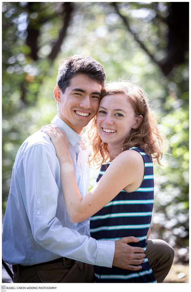 man and woman arms around each other, looking at the camera and smiling