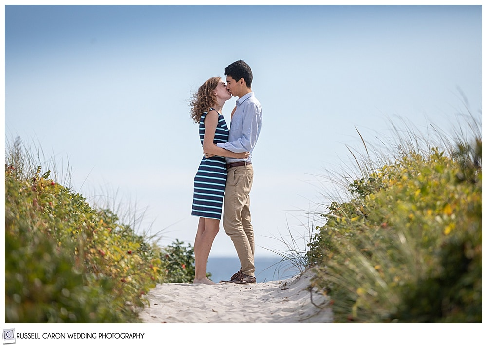 man and woman, standing face to face in the beach dunes, on a path, kissing each other
