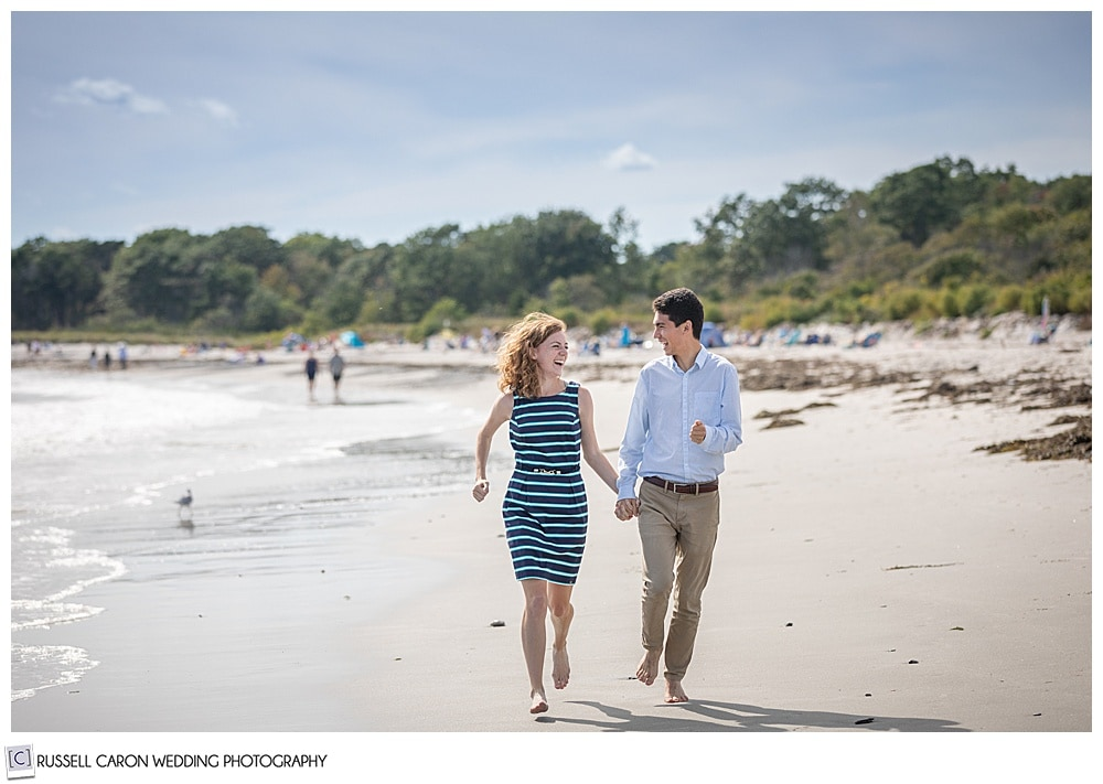 man and woman holding hands and running, they're looking at each other, during their fun crescent beach engagement