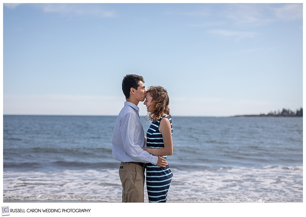 man and woman, standing face to face by the ocean, the man is kissing the woman on the forehead, during their fun crescent beach engagement session, Cape Elizabeth, Maine