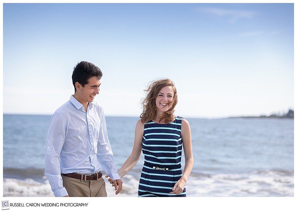 man and woman, holding hands, laughing by the ocean, the woman is looking at the camera