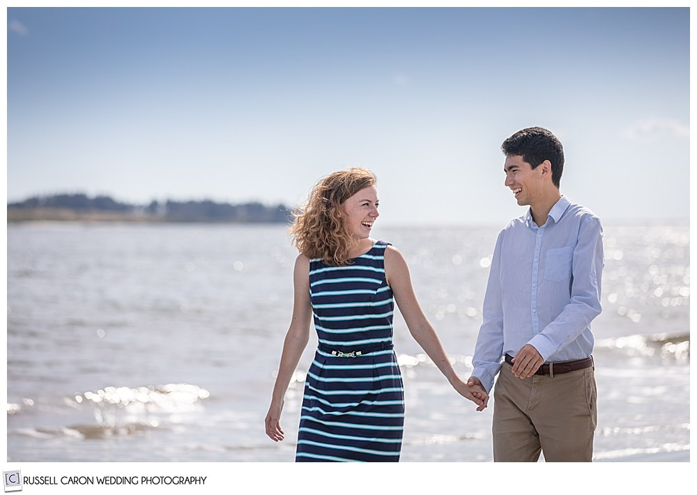 man and woman holding hands, smiling at each other, as they walk along on their fun crescent beach engagement session, cape elizabeth, maine