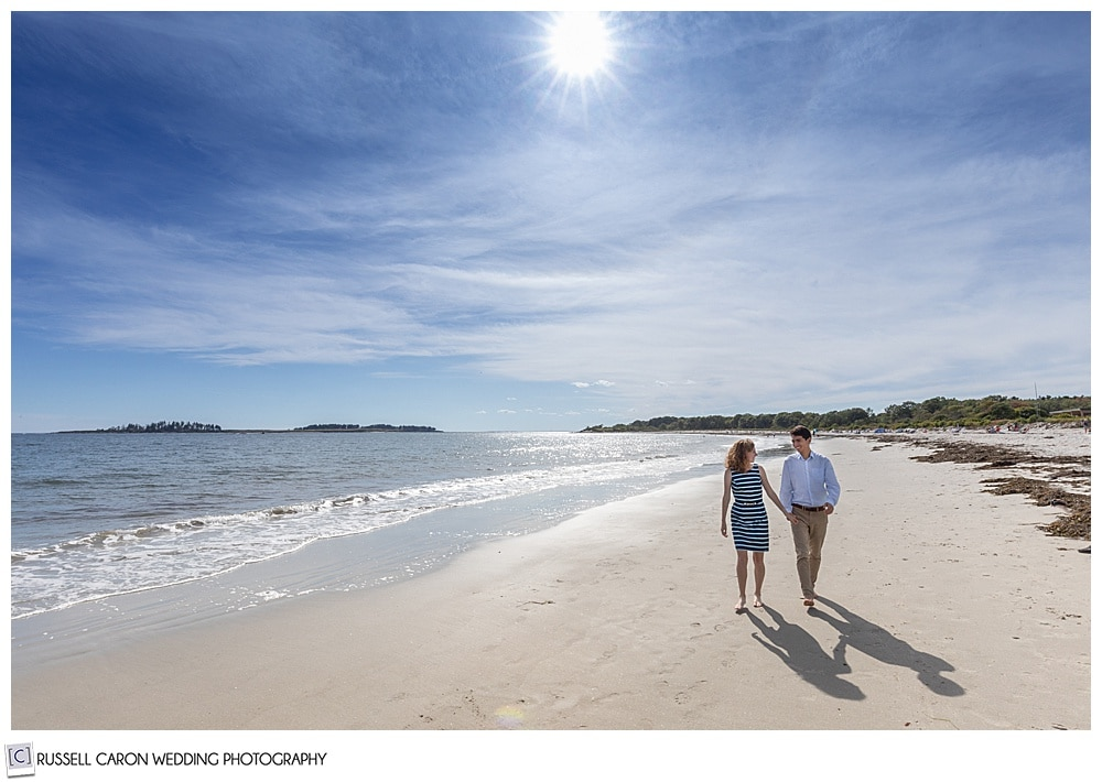 man and woman holding hands and walking on crescent beach, Cape Elizabeth, during their fun crescent beach engagement session
