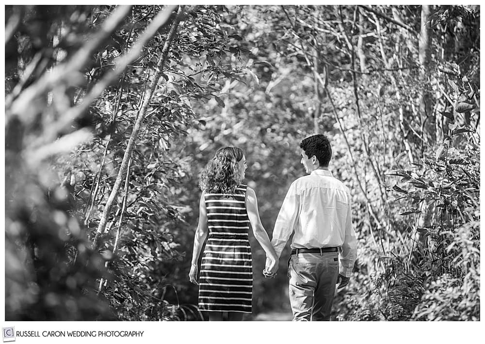 black and white photo of a man and woman, holding hands, walking in the woods