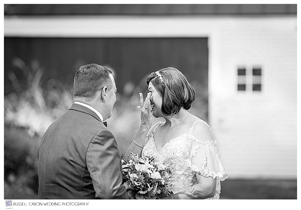 bride wipes a tear during wedding day first look