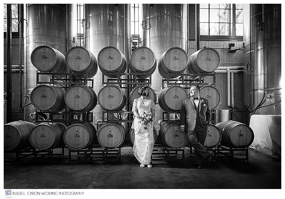 Black and white photo of bride and groom in front of the wine casks at LaBelle Winery