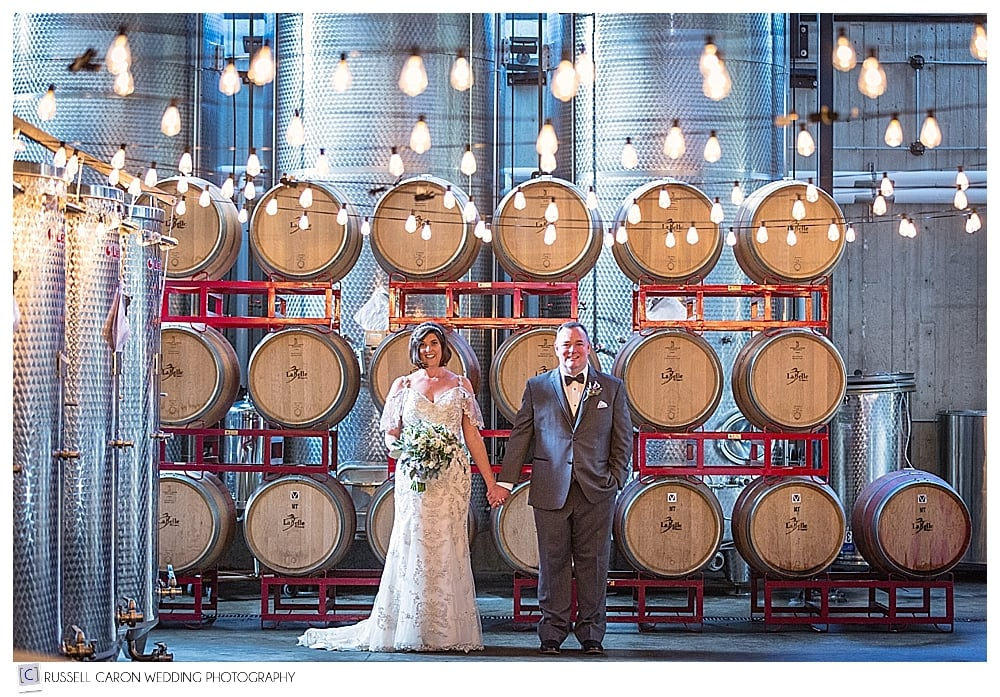 bride and groom standing in front of the wine barrels at LaBelle Winery