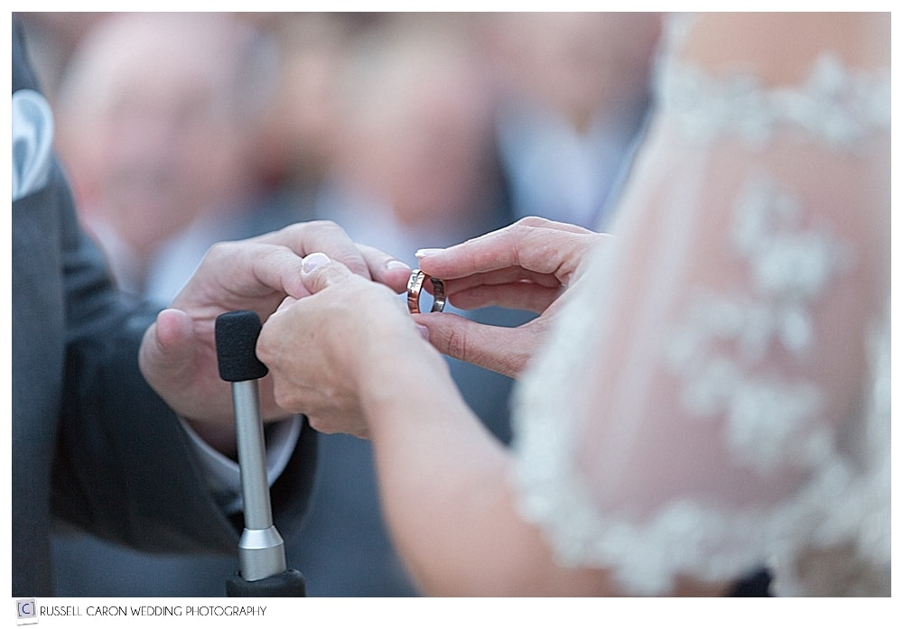 bride putting wedding band on the groom's finger