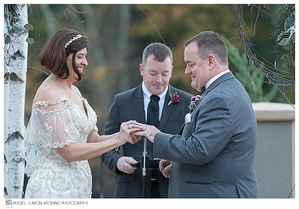 photo of bride and groom as bride puts wedding band on groom's finger