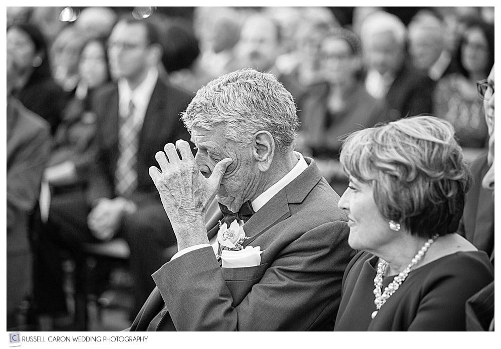 father of the bride wipes a tear during wedding ceremony