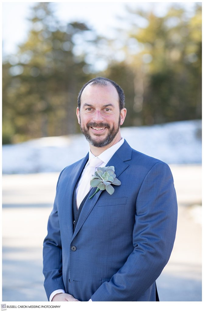 portrait of a groom wearing a blue suit