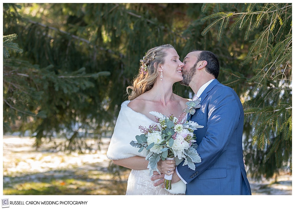groom kissing bride on her cheek during their first look