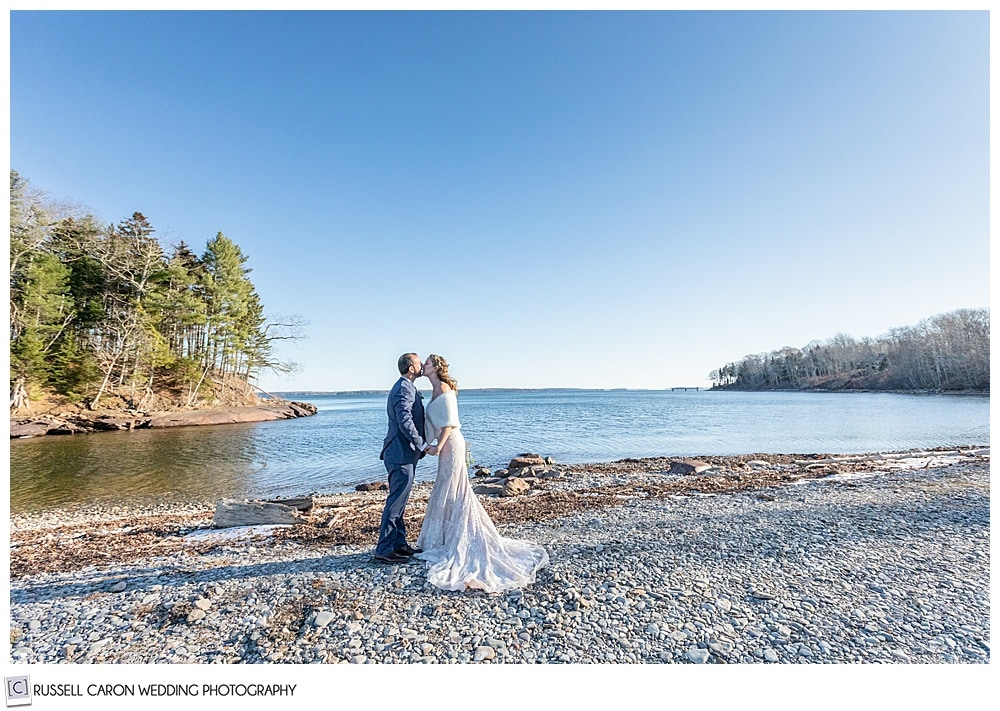 bride and groom kissing on a beach in Maine