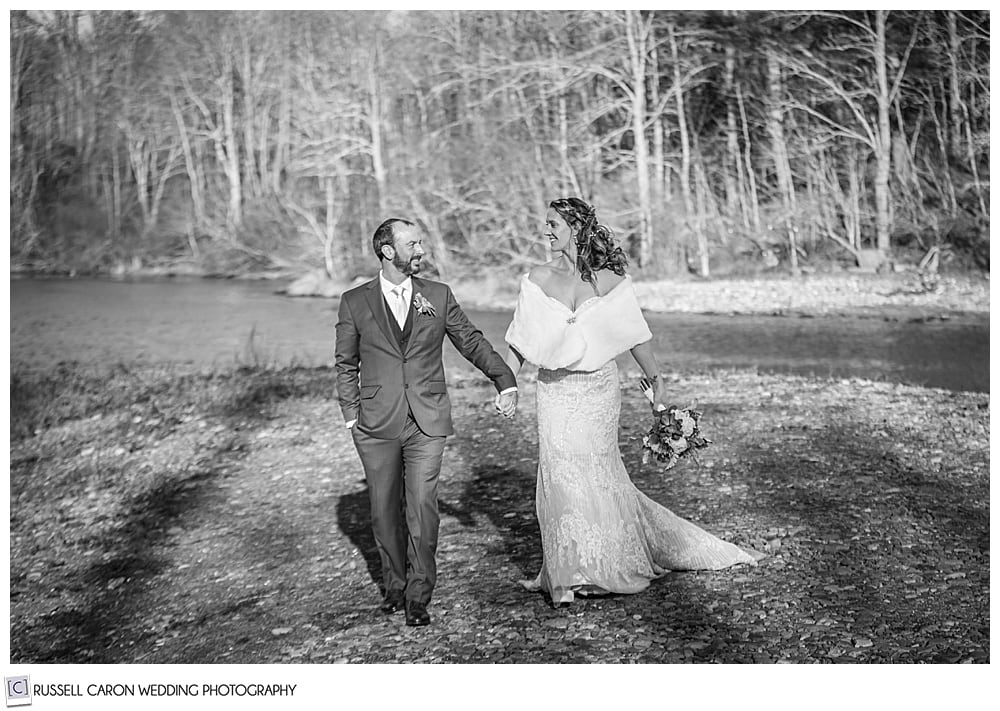 black and white photo of a bride and groom walking hand in hand