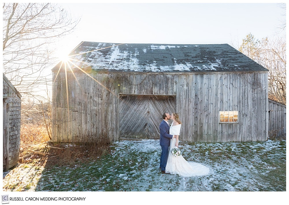bride and groom kissing in front of an old barn