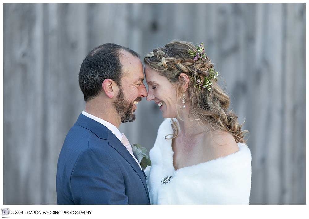bride and groom smiling and standing with their foreheads together