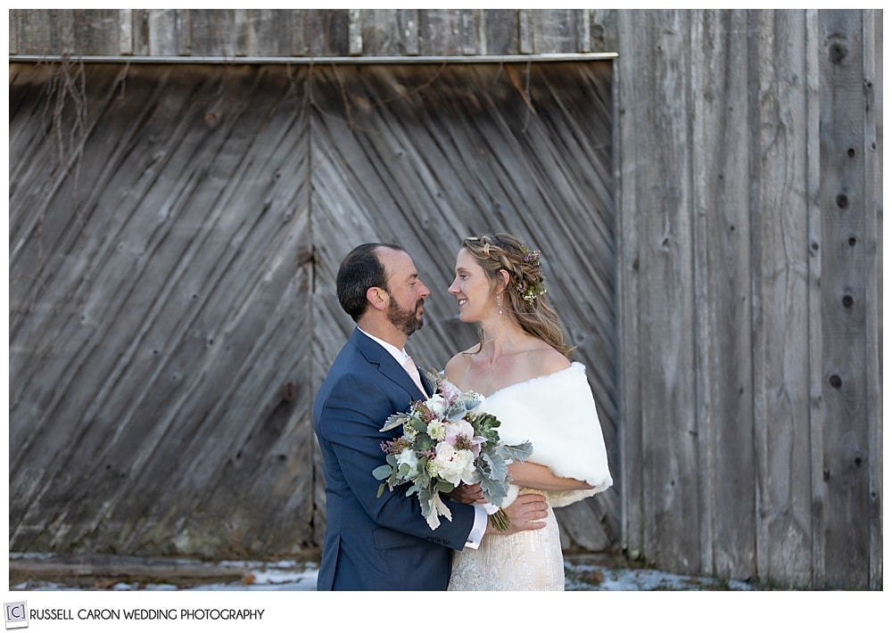 bride and groom in front of an old barn