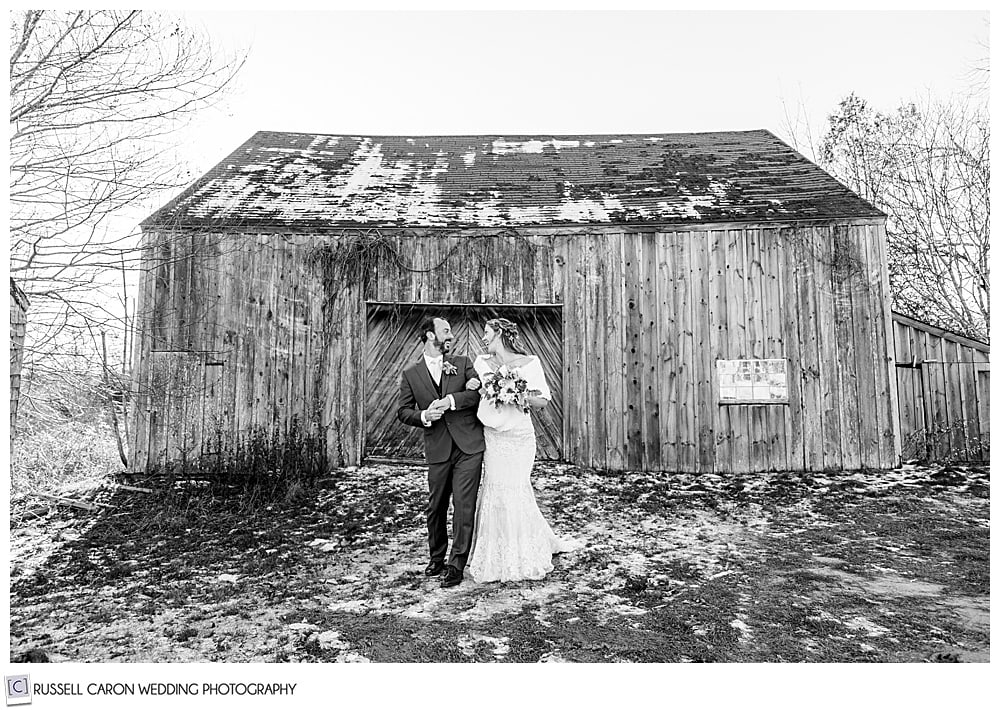 black and white photo of a bride and groom walking side by side in front of an old barn