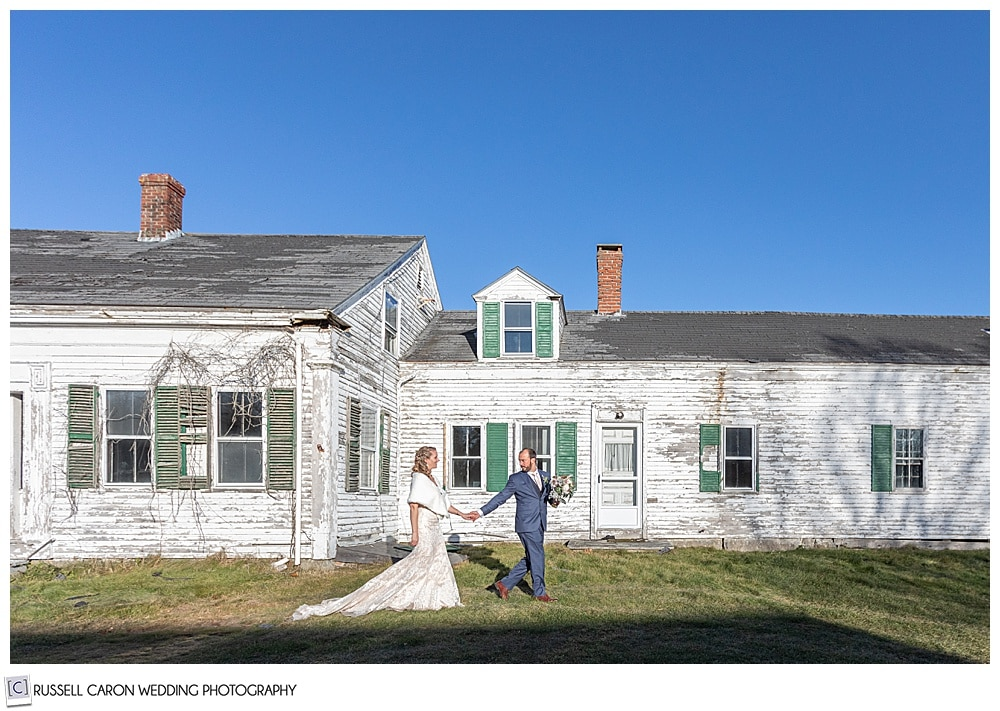 bride and groom walking in front of an old house