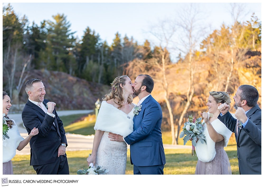 bride and groom kissing while their bridal party cheers