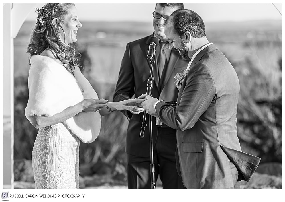 black and white photo of a groom putting the wedding band on his bride's finger during their midcoast maine wedding ceremony at Northport maine